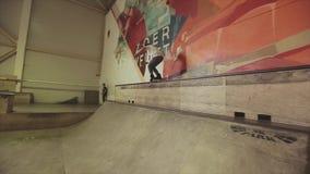De sprong van de rolschaatser op rand van springplank in skatepark dia uitdaging competition cameraman stock footage