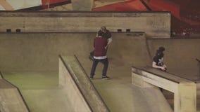 De sprong van de rolschaatser over omheining op wedstrijd in skatepark uitdaging competition cameraman extreem stock videobeelden