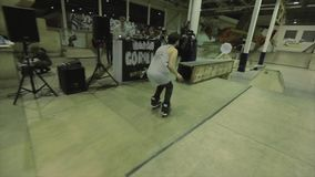 De sprong van de rolschaatser van één omheining op een andere in beweging ontbreek extreem Concurrentie in skatepark stock footage