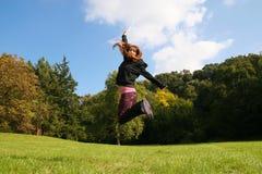 De sprong van het meisje op de weide Stock Foto's