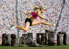 De Sprongen van de atleet over Stonehenge met een Menigte stock afbeeldingen