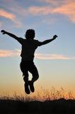 De sprongen van de mens in lucht met erachter zonsondergang Royalty-vrije Stock Afbeelding