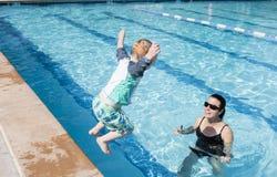 De Sprongen van de peuterjongen in Pool met Moeder die hem wachten te vangen Royalty-vrije Stock Fotografie