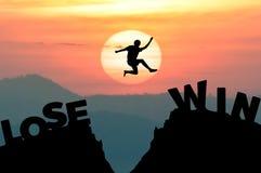 De sprongen van de silhouetmens krijgen vanaf LOSE om met zonsopgang TE WINNEN Stock Foto