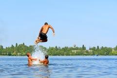 De sprongen van de tiener in water Stock Foto