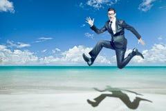 De sprongen van de zakenman in zwart kostuum op tropisch strand. stock afbeeldingen