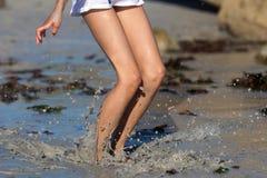 De sprongen van het meisje in modderig water Stock Foto's