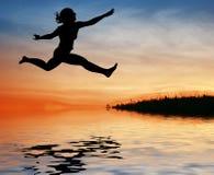 De sprongmeisje van het silhouet op water Stock Foto