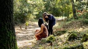 De spruit van de manierfoto in bosfotograaf met vrouwelijk model stock videobeelden