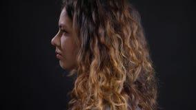 De spruit van het close-up zijaanzicht van jong aantrekkelijk Kaukasisch vrouwelijk gezicht met donkerbruin krullend haar die voo royalty-vrije stock afbeeldingen