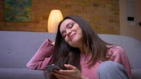 De spruit van het close-up zijaanzicht van jong gelukkig donkerbruin Kaukasisch wijfje gebruikend de telefoon en glimlachend zitt stock video