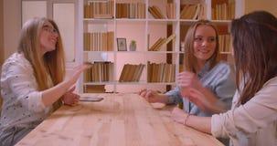 De spruit van het close-up zijaanzicht van jong mooi lesbisch paar die aan vrouwelijke makelaar in onroerend goed over aankoop va stock video