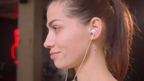 De spruit van het close-up zijaanzicht van het jonge aantrekkelijke atleet vrouwelijke puttting op haar vibes en het bekijken cam stock videobeelden