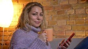 De spruit van het close-up zijaanzicht van volwassen Kaukasisch blondewijfje die op de telefoon doorbladeren terwijl het zitten o stock videobeelden
