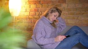 De spruit van het close-up zijaanzicht van volwassen Kaukasisch blondewijfje die de tablet gebruiken terwijl het zitten op de laa stock videobeelden