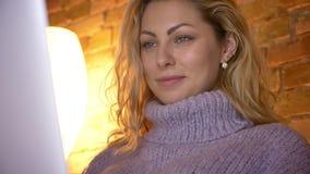 De spruit van het close-up zijaanzicht van het volwassen Kaukasische aantrekkelijke vrouwelijke typen op laptop binnen in een com stock footage