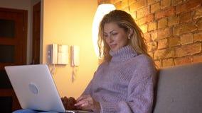De spruit van het close-up zijaanzicht van het volwassen Kaukasische aantrekkelijke vrouwelijke typen op laptop terwijl binnen he stock video