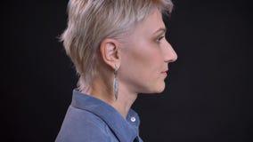 De spruit van het close-up zijaanzicht van volwassen vrij Kaukasisch vrouwelijk gezicht met kort blondehaar die vooruit met achte stock foto