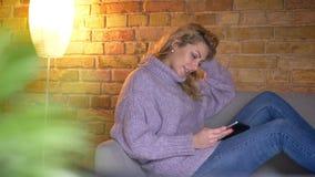 De spruit van het close-upprofiel van volwassen Kaukasisch blondewijfje die de tablet gebruiken terwijl het zitten op de laag bin stock videobeelden