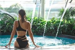De spruit van rug van sexy slank wijfje in zwempak zit op rand van zwembad tussen groene struiken op dak met stad scape stock afbeeldingen