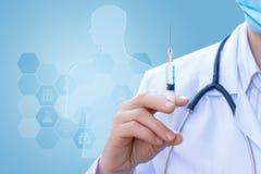 De spuit in doctor& x27; s handen met vaccin stock afbeelding