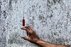 De spuit met de in hand drug , Menselijke hand met drugs narcot Royalty-vrije Stock Afbeelding