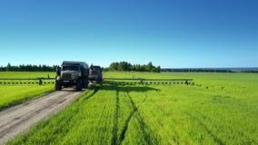 De spuitbus van het tractorgebied achter tankwagen op asfaltweg op plattelandsgebied stock footage