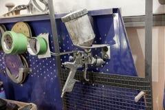 De spuitbus van de lichaamsverf op een blauwe werkbank in een voertuig dat wordt geïnstalleerd aangaande royalty-vrije stock afbeeldingen