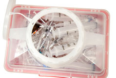De spuiten en pipets in een sharpscontainer. Stock Foto