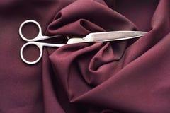 De staalschaar op de stof van Bourgondië Royalty-vrije Stock Foto