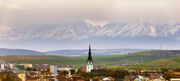 De stad en de piek van kathedraaltoren sneeuw-caped erachter bergen stock afbeeldingen