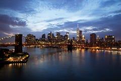 De Stad Manhattan van New York de stad in met de Brug van Brooklyn bij schemer Stock Afbeelding
