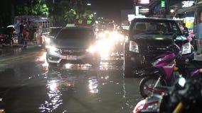 De stad van de avondnacht van Pattaya, Thailand na een sterke tropische stortbui, die auto's en mensen overgaan Zware regen op de stock footage