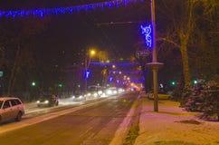 De stad van de avondwinter in het licht van de lantaarns van de straatverlichting De straat is verfraaid voor het Nieuwjaar royalty-vrije stock foto