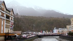 De stad van de bergtoevlucht van rivier en kabelwagen Kleurrijke toevluchtstad met stromende rivier op achtergrond van bergbos stock videobeelden