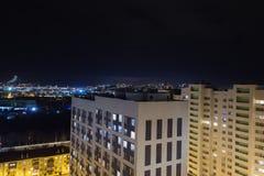 De stad van de nacht Breed hoekpanorama met residental high-rise en kleine gebouwen Verkeer vage lichten op weg stock afbeelding