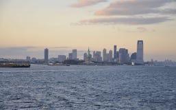 De Stad van New York, 2 Augustus: De Stadshorizon van New Jersey en Standbeeld van Vrijheid bij zonsondergang over Hudson-rivier Royalty-vrije Stock Foto