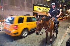 De STAD van NEW YORK, de V.S. - de Politieman berijdt haar paard Stock Foto's