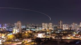 De stad van Sao Paulo bij nacht met vliegtuigsleep Stock Foto's