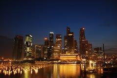 De stad van Singapore bij avond Stock Afbeelding