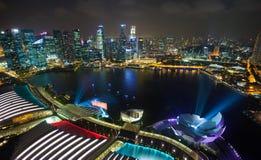 De stad van Singapore bij nacht met laser toont Stock Foto