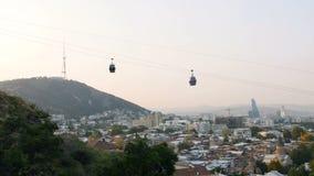 De stad van Tbilisi wordt levendig en bezig in de ochtend, Georgië, cabines die omhoog door ropeway komen stock videobeelden