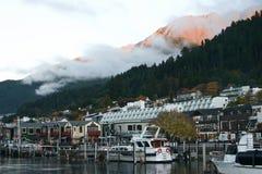 De stad van de waterkant met ochtend oranje zonlicht op berg stock fotografie