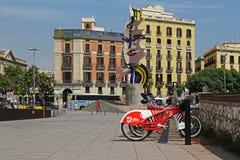 De stadsfietsen bevinden zich op een rij op een parkeren voor huur tegen de achtergrond van het beeldhouwwerk ` Barcelona hoofd`  Stock Fotografie