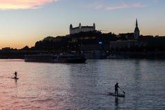 De stadshorizon van Bratislava en de rivier van Donau met peddel inschepende mensen bij de zonsondergang, Bustehouder stock foto's