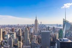 De Stadshorizon van New York in Manhattan de stad in met Empire State Building en wolkenkrabbers op zonnige dag met duidelijke bl stock fotografie