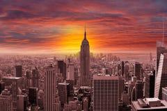 De Stadshorizon van New York met een Zonsondergang Stock Afbeeldingen
