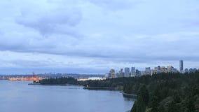 De Stadshorizon van Vancouver BC Canada met het Bewegen van Wolken en Verkeer langs Stanley Park Seawall bij Blauw Uur