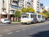 De stadstram gaat langs de Boulevard Corneliu Coposu in BucharThe-stadstram gaat langs de Boulevard Corneliu Coposu in Buchares Stock Afbeelding
