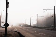 De de stadsweg of straat met autoverkeer in de ochtendlente vertroebelt of nevel, atmosferische stedelijke foto royalty-vrije stock foto